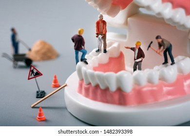 dental treatment concept - construction workers figurines on tooth model