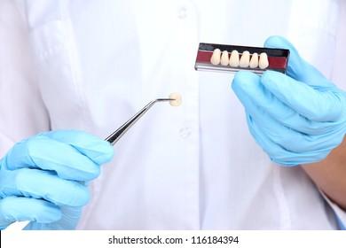 Dental tweezers and denture in dentists hands