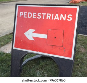 Dented and banged up red sign with the word pedestrians