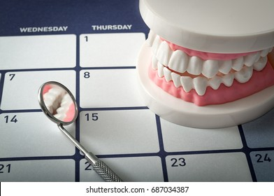 Dentist appointment, dentistry instruments and dental hygienist checkup concept with teeth model dentures and mouth mirror on a dark blue calendar. Regular checkups are essential to oral health