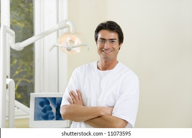dentist with arms folded smiling and standing in his office
