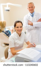 Dentist with assistant smiling at stomatology office professional health care