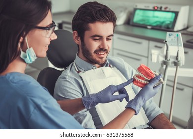 At the dentist. Beautiful female dentist is showing a dummy jaw to handsome young patient in chair