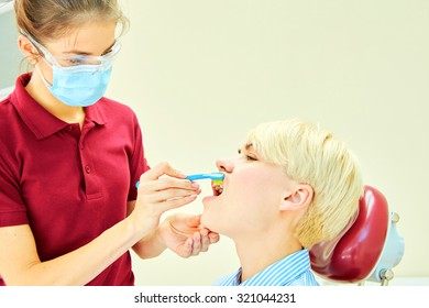 dentist brushing teeth to her patient in dental clinic
