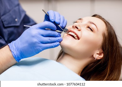 Dentist check-up teeth to young woman patient in clinic.