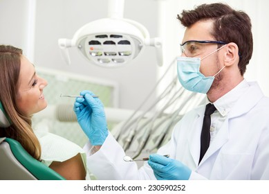 Dentist is curing a female patient at dentist's office.