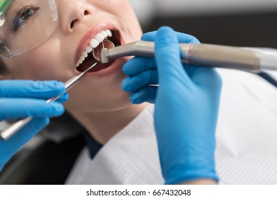 Dentist curing oral cavity of cheerful woman
