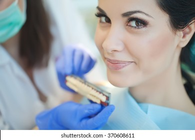 Dentist curing a woman patient in the dental office in a pleasant environment. There are specialized equipment to treat all types of dental diseases in the office.