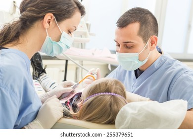 Dentist and dental assistant examining young girl teeth. Dentist is a male, assistant and patient are females. Patient is a young girl, she's smiling and not scared of dentist.