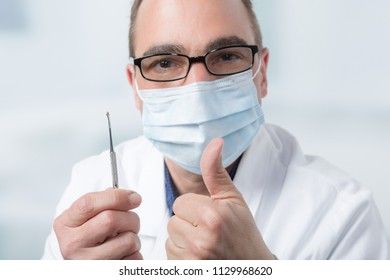 dentist with dental instrument shows thumb up