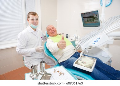 Dentist doctor and old senior man patient showing thumb up, smiling and happy looking at the camera