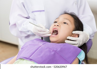 Dentist examine asian girl patient