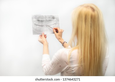 A dentist examines orthopantomogram in her hands against the background of the dentist tool