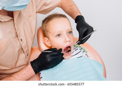 dentist examines a patient in the dental chair on a white background
