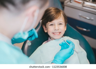 Dentist examining  boy's teeth in clinic. A small patient in the dental chair smiles. Dantist treats teeth