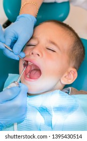 Dentist examining boy's teeth in clinic. A small patient in the dental chair smiles. Dantist treats teeth. close up view of dentist treating teeth of little boy in dentist office. vertical photo