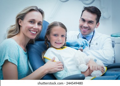 Dentist examining girls teeth in the dentists chair with assistant