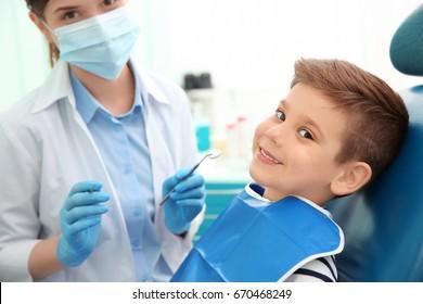 Dentist examining little boy's teeth in clinic