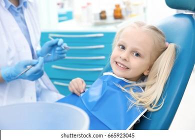 Dentist examining little girl's teeth in clinic
