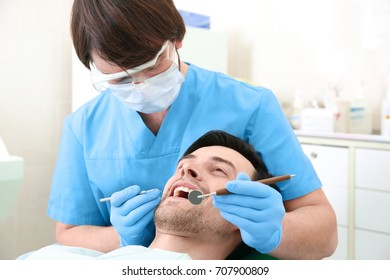 Dentist examining man's teeth in clinic