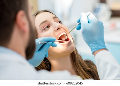 Dentist examining patient teeth with a mouth mirror and dental excavator. Close-up view on the woman's face