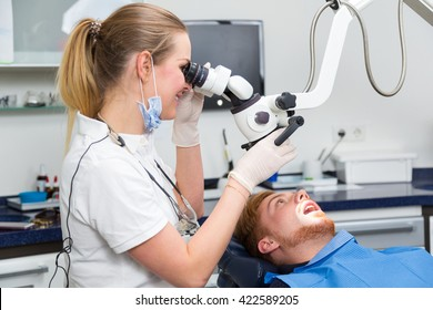 Dentist examining patient's teeth by using a microscope