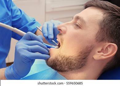 Dentist examining patient's teeth in clinic, closeup