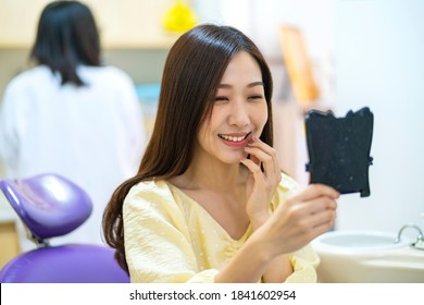 Dentist with face mask checking up Asian female teeth in Dental office. Dental care, Medical care, Lifestyle, Dental clinic or dental procedure concepts