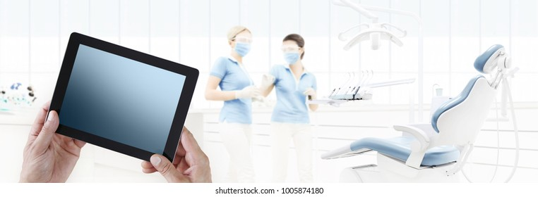 dentist hand touch digital tablet screen on dental clinic with dentist's chair background web banner template copy space contact us concept