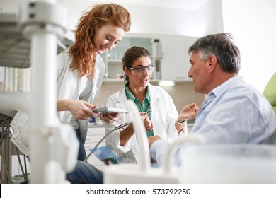 Dentist and her female assistant in dental office talking with senior patient and preparing for treatment.