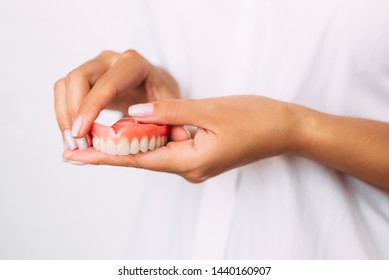 The dentist is holding dentures in his hands. Dental prosthesis in the hands of the doctor close-up. Dentistry conceptual photo. Prosthetic dentistry. False teeth. Removable denture