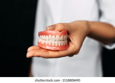 The dentist is holding dentures in his hands. Dental prosthesis in the hands of the doctor close-up. Front view of complete denture. Dentistry conceptual photo. Prosthetic dentistry. False teeth