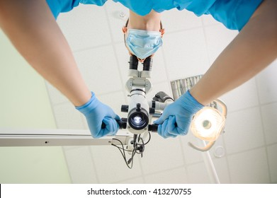 Dentist holding a microscope first-person view from below. Doctor with a microscope in a dental clinic. Oral procedure concept.