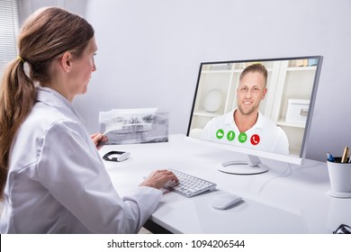 Dentist Holding Teeth X-ray While Video Conferencing With Man On Computer