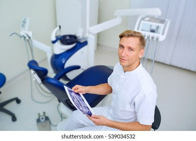 Dentist with image in the hands of workplace hospital his office