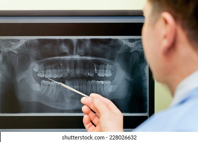 Dentist looking teeth on digital X-Ray computer monitor