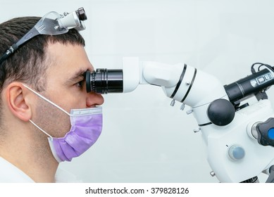 Dentist looking through a microscope in a modern clinic
