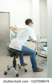 Dentist with lower back pain stretching his body  in the office