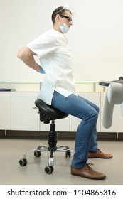 Dentist with lower back pain at work in his office in his office