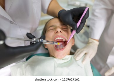 Dentist makes anesthetic injection in the gum, close up.