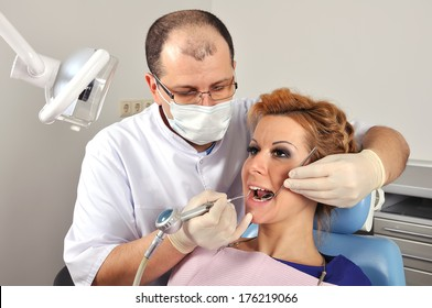 Dentist makes cleaning a patient's teeth