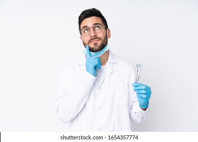 Dentist man holding tools isolated on white background thinking an idea