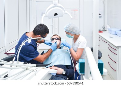 Dentist and nurse carried out the tooth of the patient treatment male patient in a dental office.