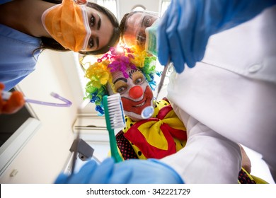 Dentist with nurse working in bottom view with funny colorful clown holding toothbrush