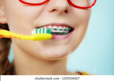 Dentist and orthodontist concept. Young woman with blue braces cleaning and brushing teeth using manual toothbrush, traditional brush