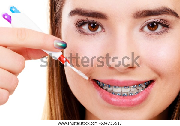 Dentist and orthodontist concept. Young woman cleaning and brushing teeth with blue braces using toothbrush