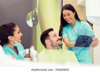 Dentist and patient looking at dental x-ray