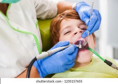 Dentist is repairing teeth of a little boy.