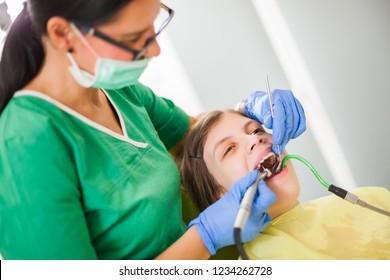 Dentist is repairing teeth of a little girl.
