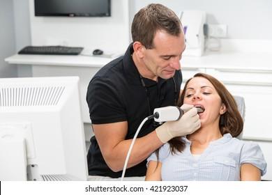 Dentist scanning patient's teeth with CEREC (Chairside Economical Restoration of Esthetic Ceramics) scanner